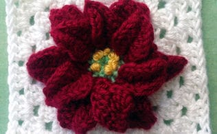 #bakingoutsidethebox | This crocheted Poinsettia Granny Square and Ornament pattern will make Christmas warm and bright. Get the pattern now. #christmascrochet #crochetpattern #grannysquare #poinsettiacrochet