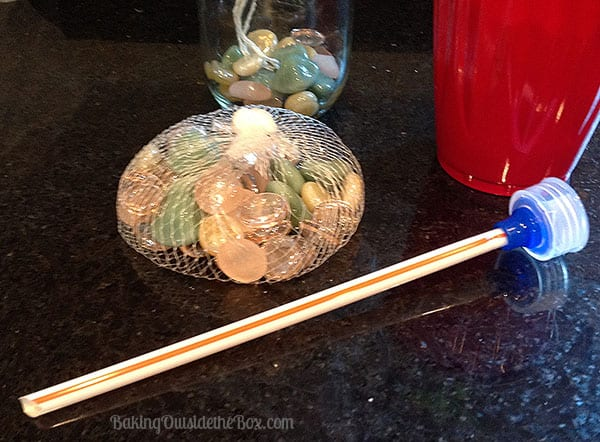 Force the plastic straw into the nozzle of the water bottle lid.